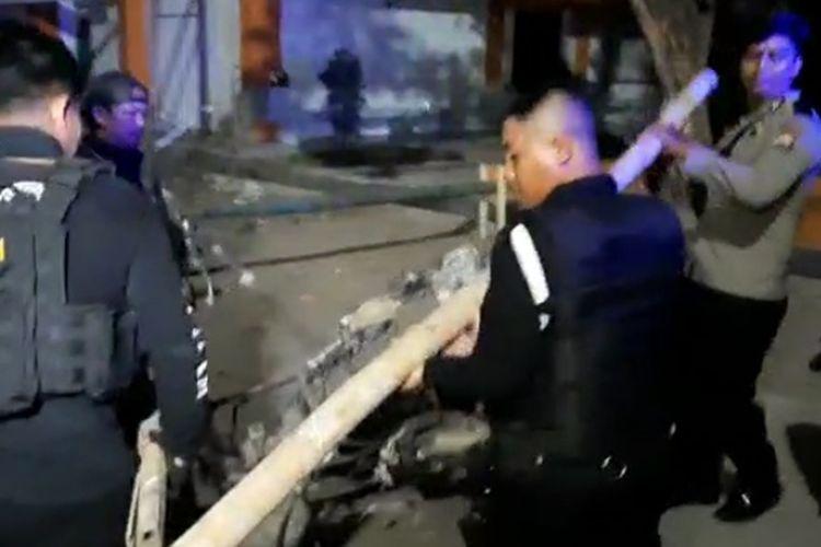 Aparat kepolisian saat membersihkan puing motor yang hangus terbakar di kampus UNM Parangtambung, Kecamatan Tamalate, Makassar, Senin (21/10/2019).