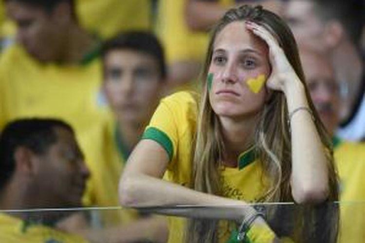 Suporter Brasil berduka atas kekalahan negaranya dalam laga melawan Jerman di semifinal Piala Dunia 2014, di Mineirao Stadium, Belo Horizonte, 8 Juli 2014. Brasil harus mengakui keunggulan Jerman dengan skor akhir 7-1.