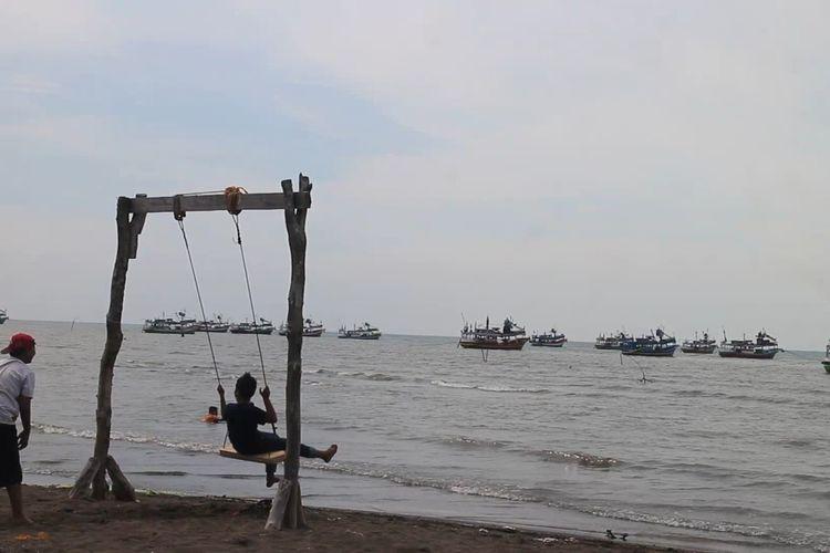 Wisatawan saat menikmati ayunan yang ada di pantai dubibir Situbondo