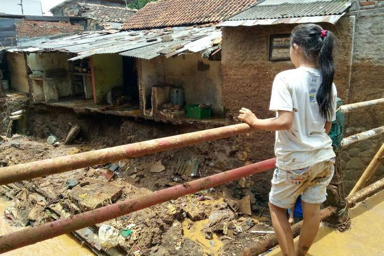 Seorang anak gadis tengah memperhatikan petugas dari Tagana Kota Bandung yang sedang membantu membersihkan puing-puing tembok rumah yang ambrol akibat gerusan air Sungai Cipamokolan, Rabu (21/3/2018).