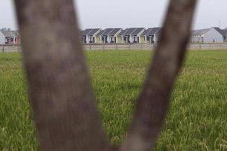 Perumahan baru di tengah areal persawahan di Kecamatan Karawang Barat, Karawang, Jawa Barat, Jumat (20/7/2012). Pengembangan kawasan industri dan perumahan berpengaruh terhadap pengurangan lahan pangan dan kondisi masyarakat.