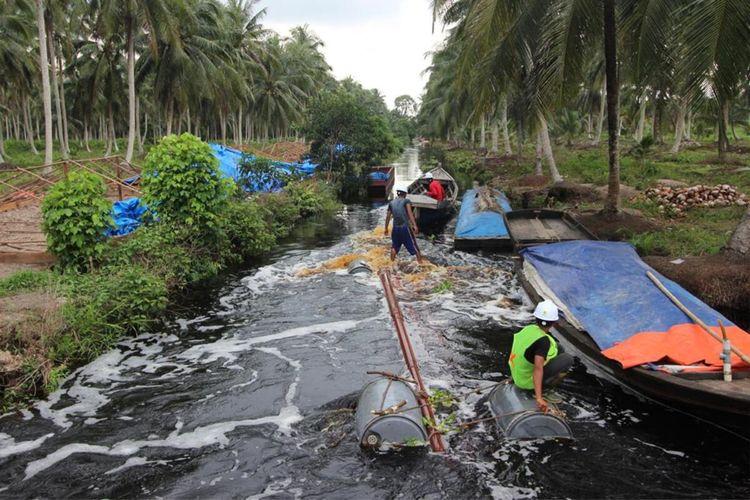 Petugas PLN berupaya mengaliri listrik dengan melintasi sungai di kawasan desa terpencil di Kabupaten Indragiri Hilir, Riau. Minggu (16/8/2020). Dok PLN-Riau/Kepri.