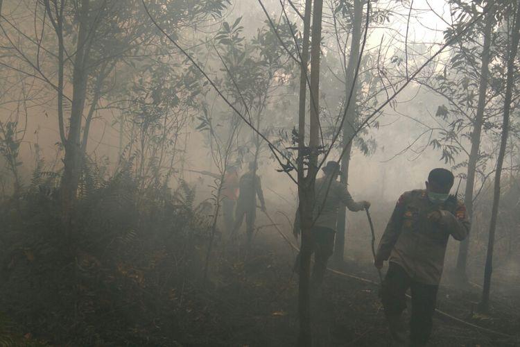 Petugas gabungan terlihat berupaya memadamkan kebakaran lahan yang terjadi di Jalan Wonodadi II, Desa Arang Limbung, Kabupaten Kubu Raya (21/2/2018)