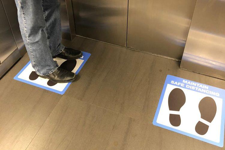 Terlihat pengumuman social distancing di dalam lift gedung NCS Hub di Ang Mo Kio, Singapura Utara. Peraturan social distancing resmi diberlakukan di Negeri ?Singa? mulai Kamis, 26 Maret 2019, pukul 23.59. Perkumpulan juga dibatasi maksimal 10 orang, dan jarak setiap orang harus paling dekat 1 meter.