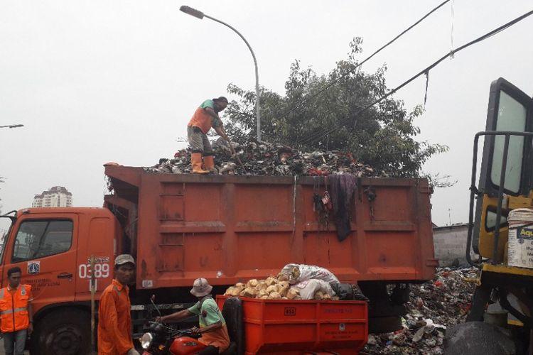 Petugas, Selasa (23/10/2018), mengangkut sampah dari TPS Muara Baru, Jakarta Utara, ke dalam truk yang akan membawa sampah ke TPST Bantargebang, Bekasi.