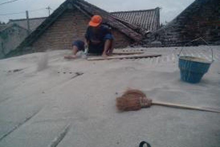 Seorang penjual jasa bersih atap saat menjalankan jasanya membersihkan atap rumah warga dari abu vulkanik erupsi Gunung Kelud, Selasa (25/2/2014). Jasa pembersih atap mulai marak usai erupsi Kelud 13 Februari 2014 lalu.