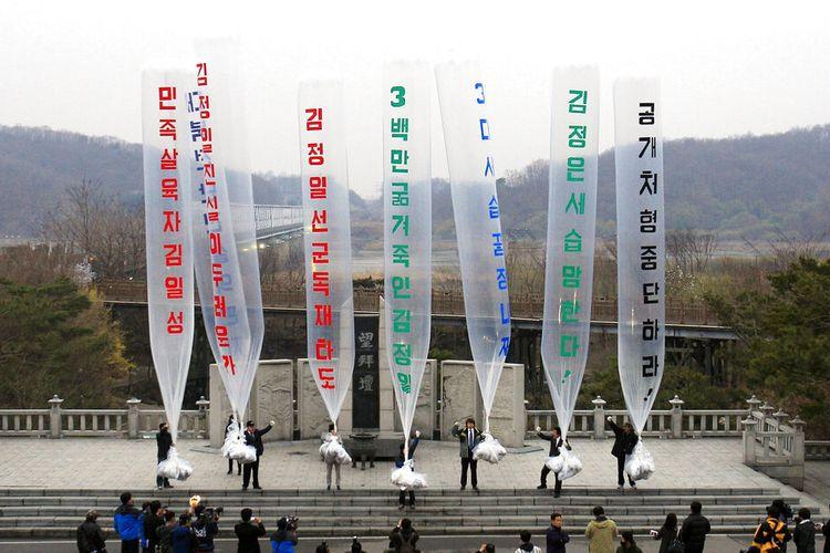 Dalam foto dari 11 April 2011, Park Sang-hak, tengah, seorang pengungsi dari Utara, yang sekarang menjalankan grup Fighters for a Free North Korea dari sebuah kantor kecil di Seoul, bersiap melepaskan balon yang membawa selebaran mengutuk pemimpin Korea Utara selama unjuk rasa anti-Korea Utara melawan The Day of the Sun, peringatan 99 tahun kelahiran Kim Il Sung, di Paviliun Imjingak dekat desa perbatasan Panmunjom di Paju, Korea Selatan.