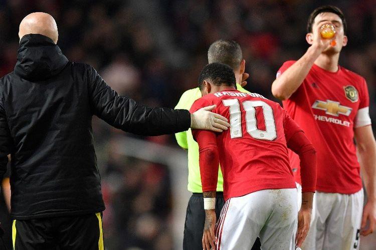 Penyerang Manchester United, Marcus Rashford, mendapat perawatan setelah terjatuh pada laga replay babak ketiga Piala FA kontra Wolverhampton Wanderers di Old Trafford, Manchester, Kamis (16/1/2020) dini hari WIB.