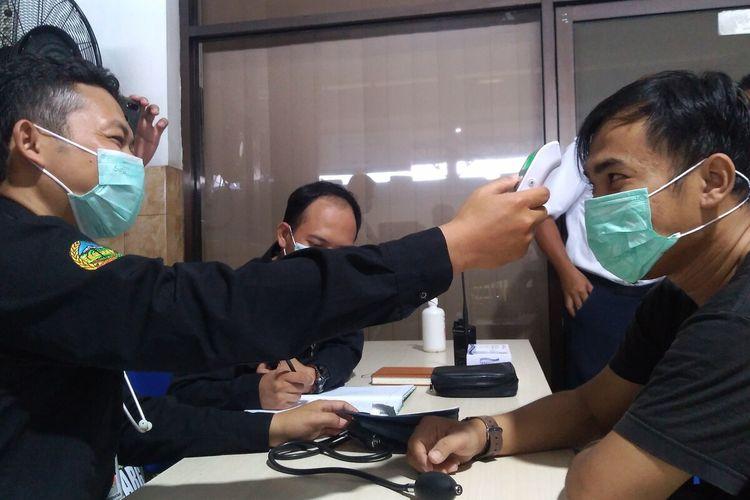 Petugas mengecek kesehatan penumpang di Stasiun Purwokerto, Jawa Tengah, Selasa (28/1/2020).