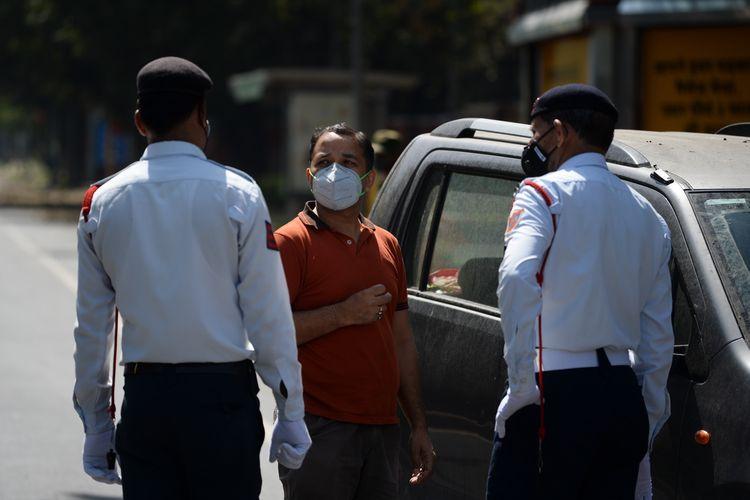 Petugas keamanan di New Delhi memeriksa pengendara pada hari pertama pemberlakuan karantina atau lockdown di seluruh wilayah di India, Rabu (25/03/2020). Perdana Menteri India Narendra Modi mengumumkan, negaranya memasuki masa lockdown total selama 21 hari untuk memerangi virus corona.