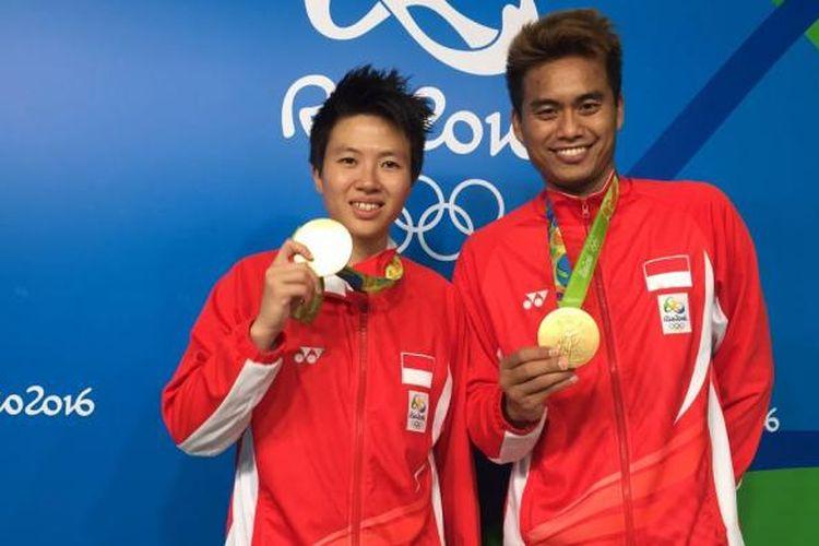 Liliyana Natsir dan Tontowi Ahmad memamerkan medali emas yang diraihnya di Olimpiade Rio 2016, Rabu (17/8/2016).