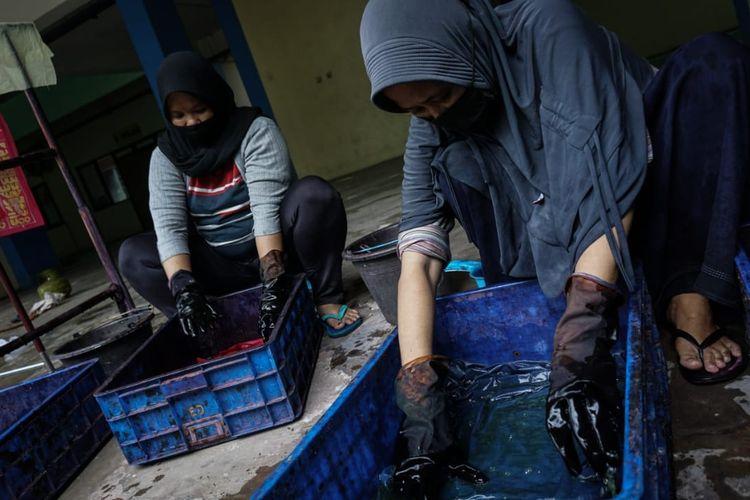 Ibu-ibu pengrajin batik tulis Rusun Pulogebang sedang mewarnai kain batik yang telah mereka lukis dengan canting, Jumat (18/6/2021).