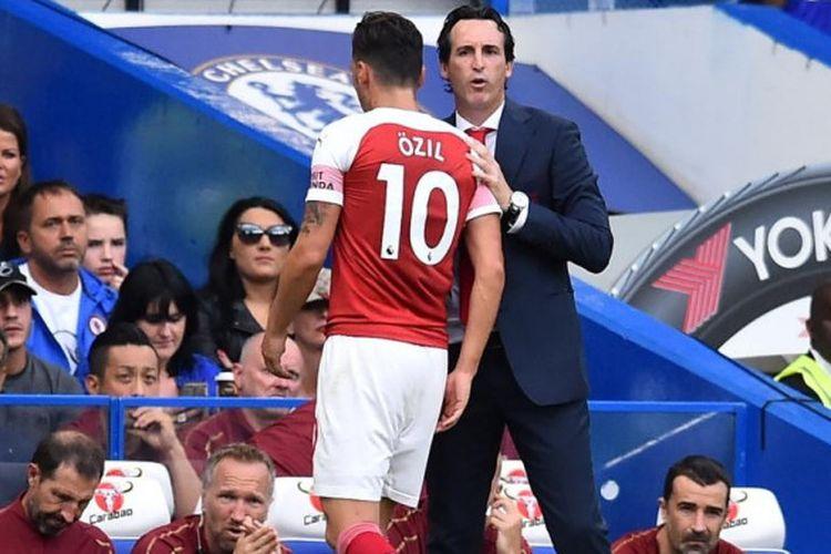 Pelatih Arsenal Unai Emery berbicara dengan Mesut Oezil dalam partai Liga Inggris di markas Chelsea, Stadion Stamford Bridge, Sabtu (18/8/2018) malam WIB.