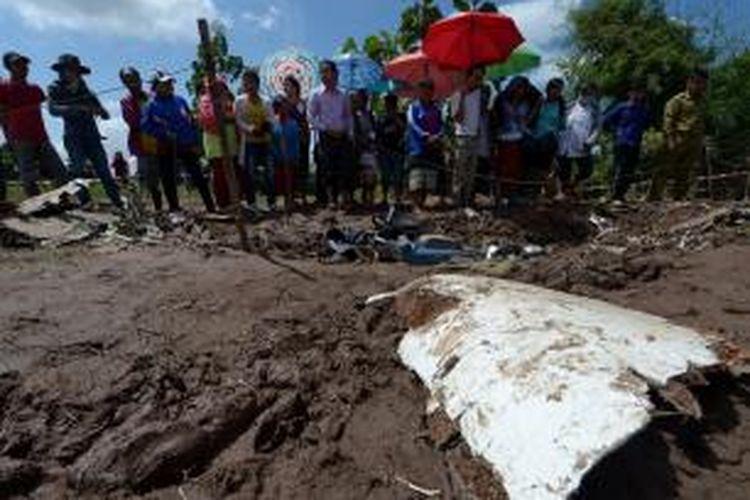 Warga desa di sekitar jatuhnya pesawat ATR-72 milik Lao Airlines memperhatikan serpihan badan pesawat naas tersebut. Pesawat Lao Airlines jatuh di Sungai Mekong, Rabu (16/10/2013), dalam penerbangan dari Vientiane menuju ke wilayah selatan negeri itu. Dari 49 penumpang dan awak, sebanyak  28 penumpang adalah warga negara asing.