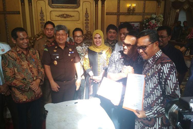 Dewan pembina Yayasan Olahraga Sulawesi Selatan (YOSS) Andi Ilham Mattalatta saat berjabat tangan dengan gubernur Sulawesi Selatan Nurdin Abdullah usai menandatangani penyerahan aset Stadion Mattoanging di rujab gubernur Sulawesi Selatan, Senin (2/3/2020).