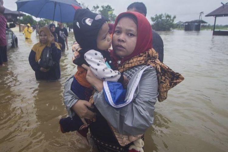 Warga menggendong anaknya melintasi banjir di Desa Kampung Melayu, Kabupaten Banjar, Kalimantan Selatan, Jumat (15/01). Banjir ini digambarkan sebagai banjir terbesar yang melanda provinsi tersebut.