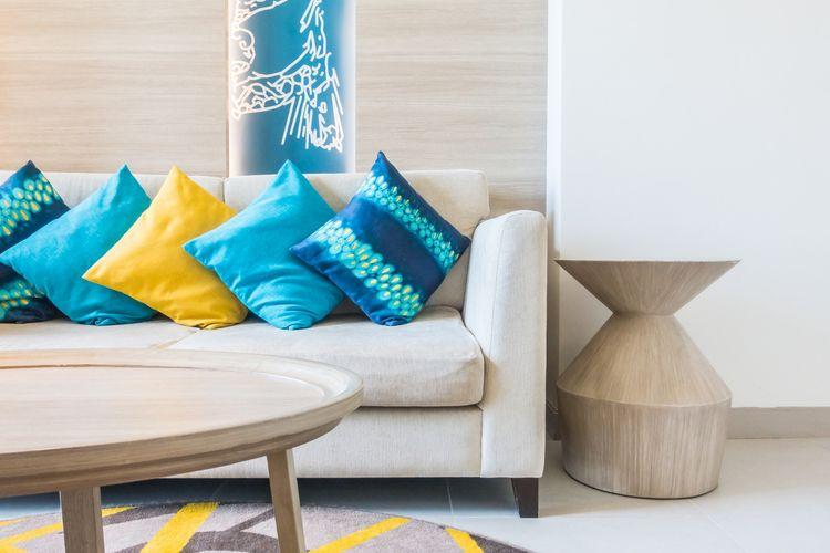 Ilustrasi sofa dengan bantal sofa beraneka warna.