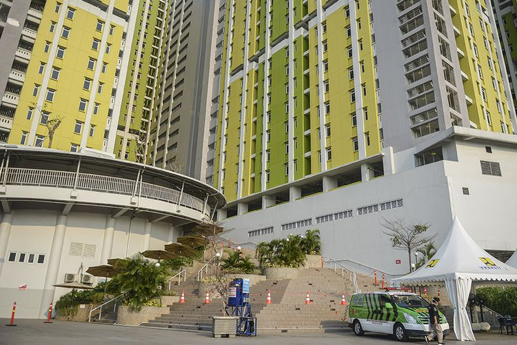 Petugas berjalan di depan ambulans di Rusun Pasar Rumput, Manggarai, Jakarta, Minggu (18/7/2021). Pemerintah mulai mengoperasikan tower satu dengan kapasitas 553 kamar yang mampu merawat 1.659 pasien terpapar COVID-19 tanpa gejala dan bergejala ringan.