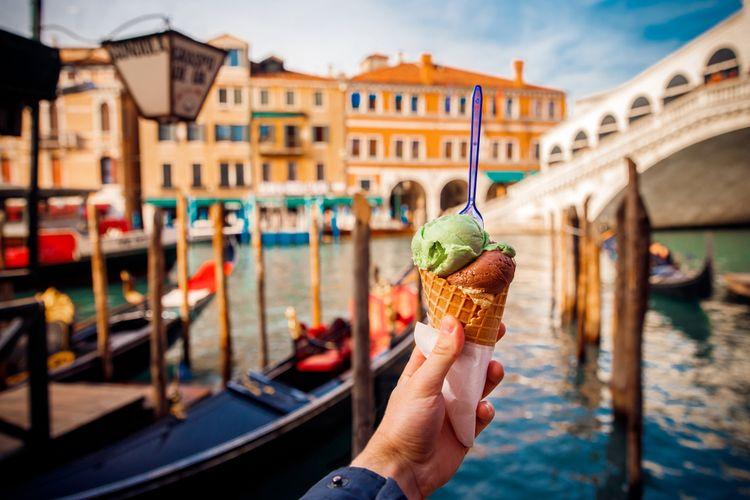 Ilustrasi seseorang memegang gelato dengan latar belakang kanal di Venesia, Italia.