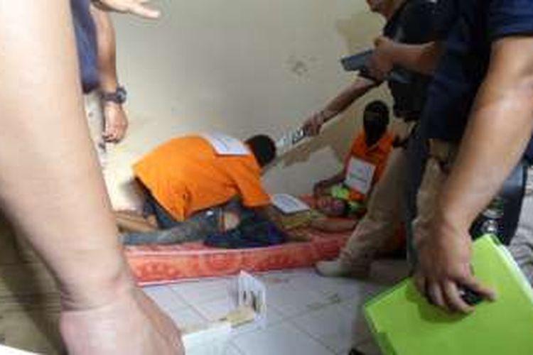 Tiga tersangka pemerkosa dan pembunuh EF (19), RA (16), Rahmat Arifin (24), dan Imam Harpiadi (24), memperagakan cara mereka membunuh di mes karyawan PT Polyta Global Mandiri, Kosambi, Kabupaten Tangerang, Selasa (17/5/2016). Dari rekonstruksi ini, diketahui para tersangka yang tidak saling mengenal, bekerja sama untuk sama-sama membunuh EF.