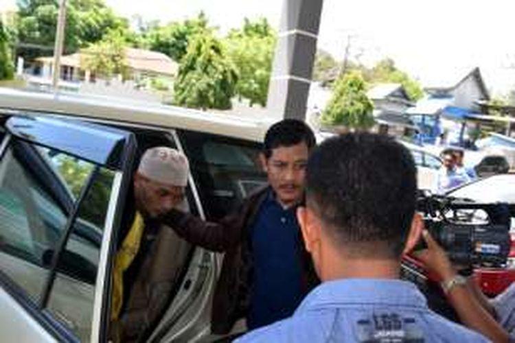 Abdul Halip Bin Muin (berpeci), anggota Kelompok Santoso, turun dari mobil di depan LP Baubau. Ia akan menjalani masa tahanan selama 4 tahun di LP Baubau