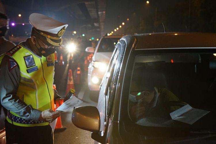 Polisi memgecek dokumen pendukung Pelaku Perjalanan Dalam Negeri (PPDN) kendaraan yang melintas di Jalan Tol Jakarta-Cikampek pada periode larangan mudik 6-17 Mei 2021