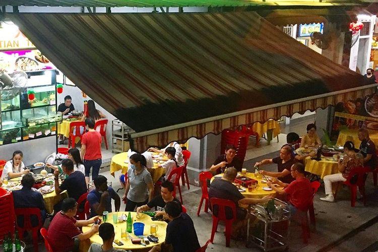 Pengunjung Restoran Seafood Tian Tian di Tiong Bahru, Singapura menunggu sambil menyantap hidangan mereka, Jumat malam (19/06/2020). Warga dapat kembali menyantap hidangan di tempat mulai Jumat hari ini yang adalah  hari pertama Fase 2 Singapura menuju new normal hidup berdampingan dengan virus Covid-19.