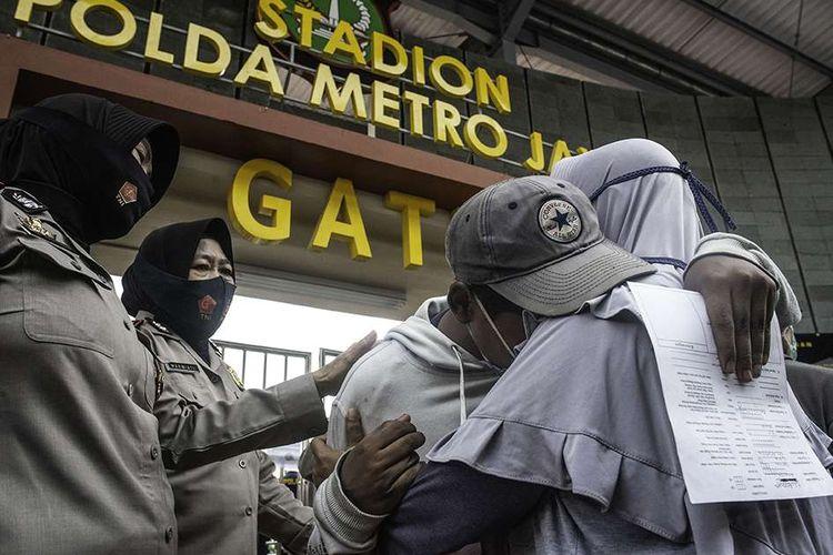 Peserta aksi memeluk orangtuanya usai dipulangkan di Polda Metro Jaya, Jakarta, Rabu (14/10/2020). Polda Metro Jaya memulangkan ratusan peserta aksi yang diamankan dalam aksi unjuk rasa menolak UU Cipta Kerja.