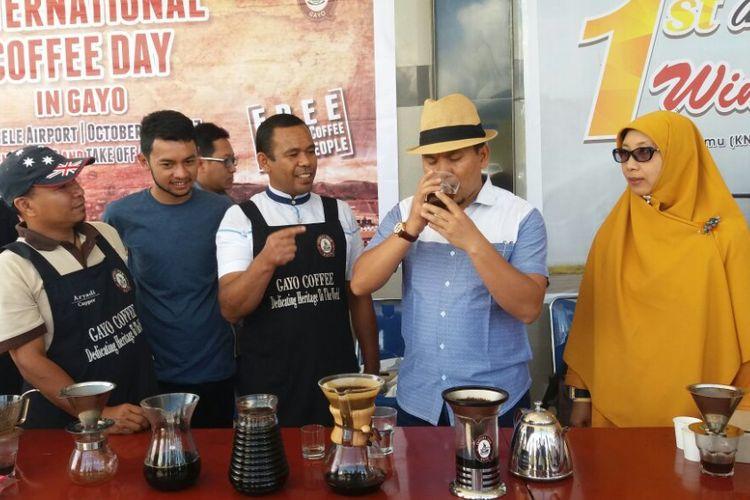 Ketua Gayo Cupper Team (GCT), Mahdi Usati, saat memberikan kopi racikannya kepada Bupati Bener Meriah dalam International Coffee Day In Gayo, Minggu (1/10/2017), di Bandara Rembele, Bener Meriah, Aceh.