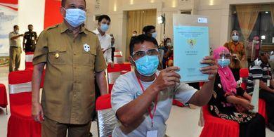 Seorang warga Gorontalo memperlihatkan sertifikat tanah yang baru dimilikinya di samping Wakil Gubernur Idris Rahim.