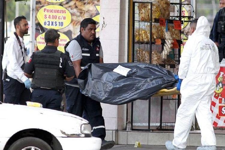 Polisi Meksiko membawa kantong jenaza berisi korban kekejaman kartel pimpinan El Mencho.
