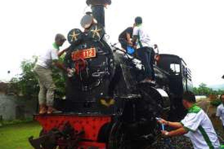 Komunitas Railfans Daop Empat tengah melakukan pencucian lokomotif seri B5112   di Museum Kereta Api Ambarawa, Selasa (28/6/2016) siang. Lokomotif seri B5112 merupakan salah satu koleksi lokomotif jenis uap yang akan dioperasikan selama libur lebaran 2016.