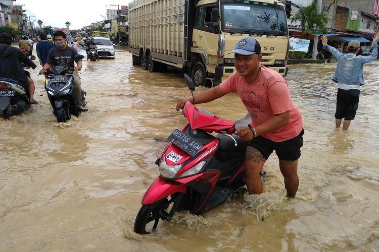 Seorang warga mendorong sepeda motornya yang mogok saat melintasi banjir di Kampung Lalang, Jalan Medan - Binjai. Banjir terjadi di sejumlah titik di Kota Medan dan sekitarnya sejak Jumat (4/12/2020) dini hari.