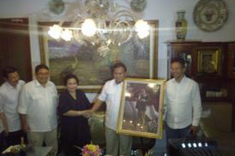 Ketua Dewan Pertimbangan DPP Partai Nasdem Rachmawati Soekarnoputri memberikan lukisan Proklamator RI Ir. Soekarno kepada Ketua Dewan Pembina DPP Partai Gerindra Prabowo Subianto, Jumat (16/5/2014).