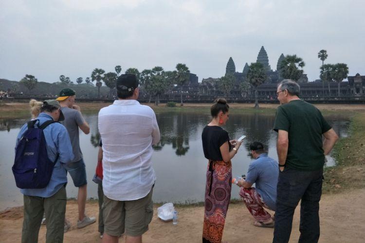 Para wisatawan berdiri di sekitar kolam untuk mengabadikan keindahan matahari terbit di Angkor Wat, Siem Reap, Kamboja, Sabtu (23/2/2019).