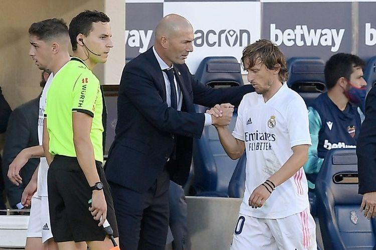 Pelatih Real Madrid Zinedine Zidane menyapa tangan gelandang Luka Modric pada laga Liga Spanyol, Levante UD vs Real Madrid, Stadion La Ceramica, 4 Oktober 2020.