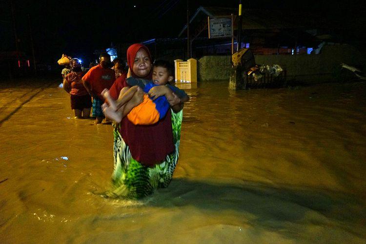 Sejumlah warga melintasi banjir untuk mengungsi ke tempat yang lebih tinggi di Kota Timur, Kota Gorontalo, Gorontalo, Kamis (11/6/2020) malam. Data sementara dari pemerintah setempat mencatat sebanyak 1.150 warga terdampak banjir dengan ketinggian air mencapai 1,5 meter.