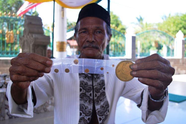 Warga memperlihatkan beragam ukuran koin emas (dirham) di Kompleks Makam Sultan Kerajaan Malikussaleh, Kecamatan Samudera, Aceh Utara