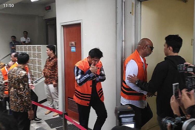 Anggota DPR Bowo Sidik Pangarso (rompi tahanan dan kemeja biru bergaris) menunjukkan jempolnya usai mencoblos di Rutan KPK, Jakarta, Rabu (17/4/2019).