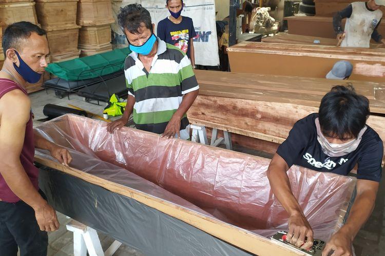 Pekerja memasang lapisan plastik pada peti mati untuk pasien Covid di Rina Florist Purwokerto, Kabupaten Banyumas, Jawa Tengah, Selasa (26/1/2021).