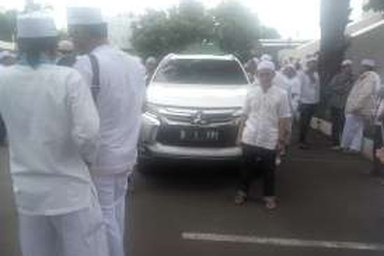 Massa saat berfoto di depan mobil milik pemimpin Front Pembela Islam (FPI) Rizieq Shihab yang terparkir di pelataran Masjid Al Azhar, Jakarta Selatan, Senin (16/1/2017).