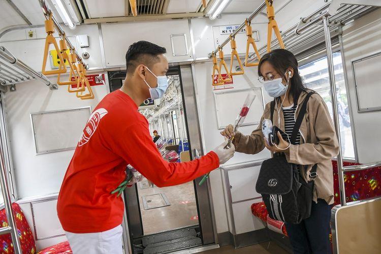 Petugas millenial KAI Commuter memberikan bunga dan healthy kit kepada perempuan pengguna KRL Commuter Line di Stasiun Jatinegara Baru, Jakarta, Selasa (22/12/2020). Memperingati Hari Ibu, PT KAI Commuter memberikan layanan istimewa khususnya perempuan dengan memberikan bunga dan healty kit sekaligus sosialisasi protokol kesehatan dengan menerapkan Adaptasi Kebiasaan Baru (AKB) di lingkungan stasiun dan di KRL. ANTARA FOTO/Galih Pradipta/foc.