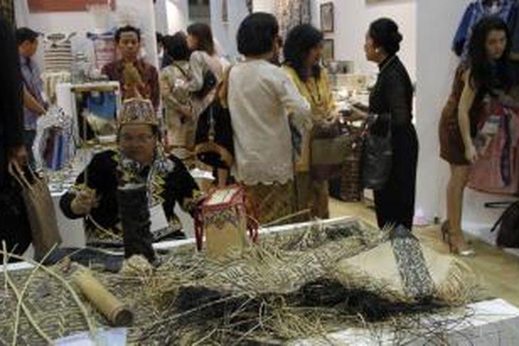Seorang perempuan dayak mendemonstrasikan kerajianan anyaman di  Rumah Indonesia di Tokyo International Gift Show (TIGS), Tokyo, Rabu (4/9/2013). Sebanyak 36 perajin Indonesia yang diinisiasi oleh Dekranas berpartisipasi dalam pameran internasional ini.