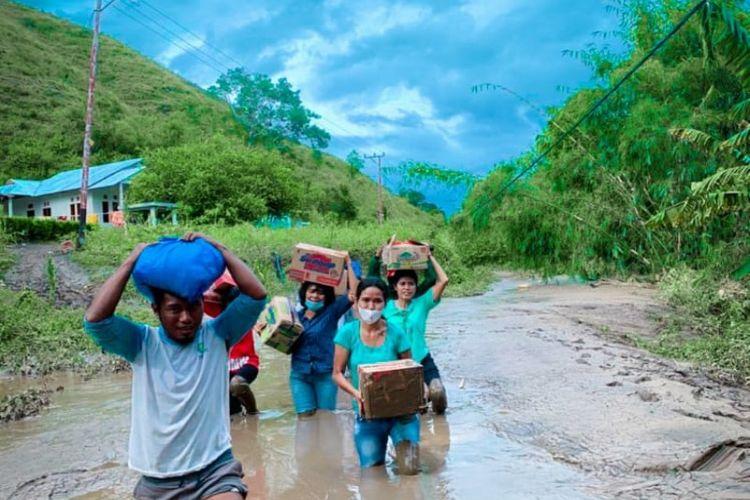 Merliaty Praing Simanjuntak (mengenakan baju kemeja) bersama sejumlah relawan muda berjibaku di jalan berlumpur saat membawakan bantuan untuk para korban banjir bandang di Desa Kiritana, Kecamatan Kambera, Kabupaten Sumba Timur, Nusa Tenggara Timur (NTT).