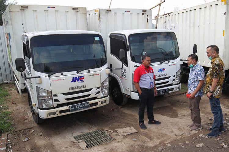 Kiri kekanan : Agus Yunanto (Deputy Branch Head JNE Express Solo), Sucipto (kepala Wilayah Astra-Isuzu Jateng dan DIY) dan M. Yusuf (Branch Manager Astra-Isuzu Solo) berbincang didepan barisan unit ISUZU ELF dan ISUZU Giga, Sabtu (14/11/2020) di Kantor JNE Solo.