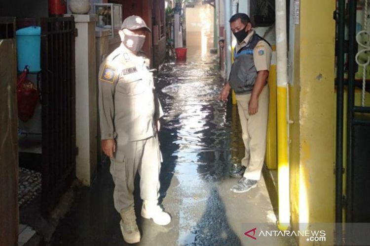 Petugas Kelurahan Bidara Cina mengecek situasi air banjir yang mulai surut di RW07, Senin (5/10/2020). Banjir di kawasan Bidara Cina terjadi akibat luapan Kali Ciliwung yang berlangsung dini hari.
