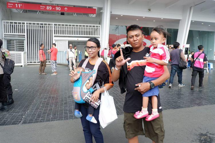Pasangan suami-istri Jakmania membawa anak mereka yang masih balita ke pertandingan Persija vs Persib di SUGBK, Senayan, Jakarta.