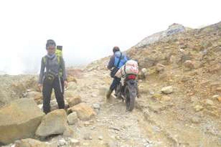 Seorang warga tengah mengendarai motor di jalur pendakian Gunung Papandayan, Garut, Jawa Barat, Sabtu (20/2/2016). Motor di Gunung Papandayan digunakan untuk mengangkut barang-barang dagangan, evakuasi pendaki, jasa porter, dan mengangkut hasil perkebunan.
