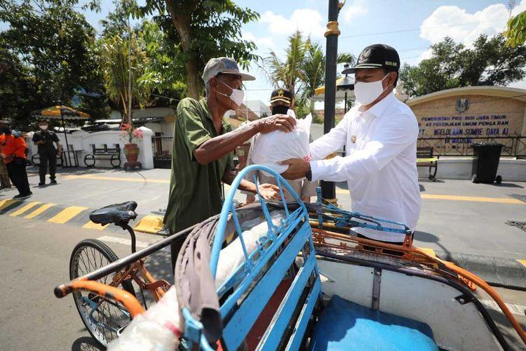 BANTUAN SEMBAKO--Walikota Madiun, Maidi menyalurkan bantuan paket sembako kepada ratusan tukang becak yang terdampak corona.