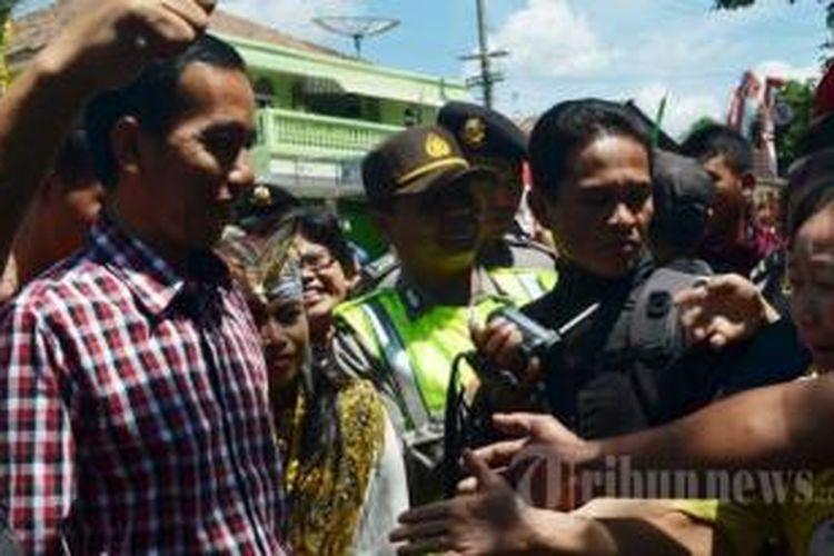 Gubernur DKI Jakarta Joko Widodo (kemeja kotak-kotak) mengikuti kampanye calon gubernur Jawa Timur, Bambang Dwi Hartono di Pasar Sayur Magetan, Minggu (18/8/2013).